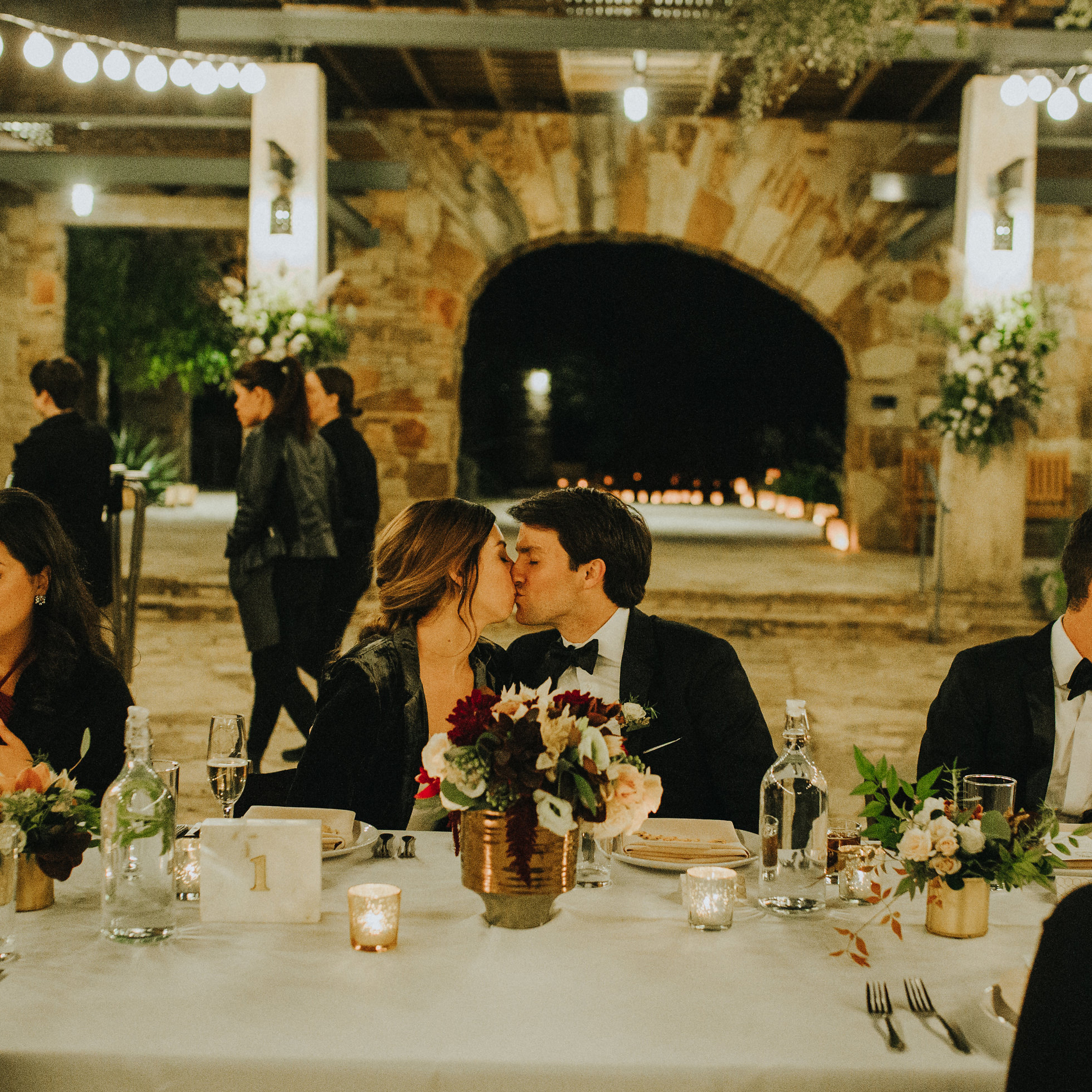 Bride and Groom kissing at wedding table