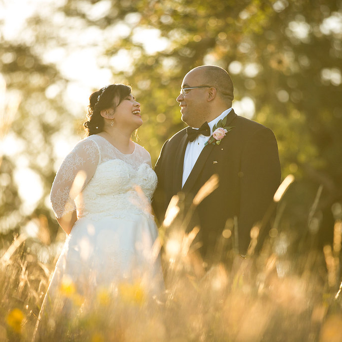 Bride and groom in a field smiling
