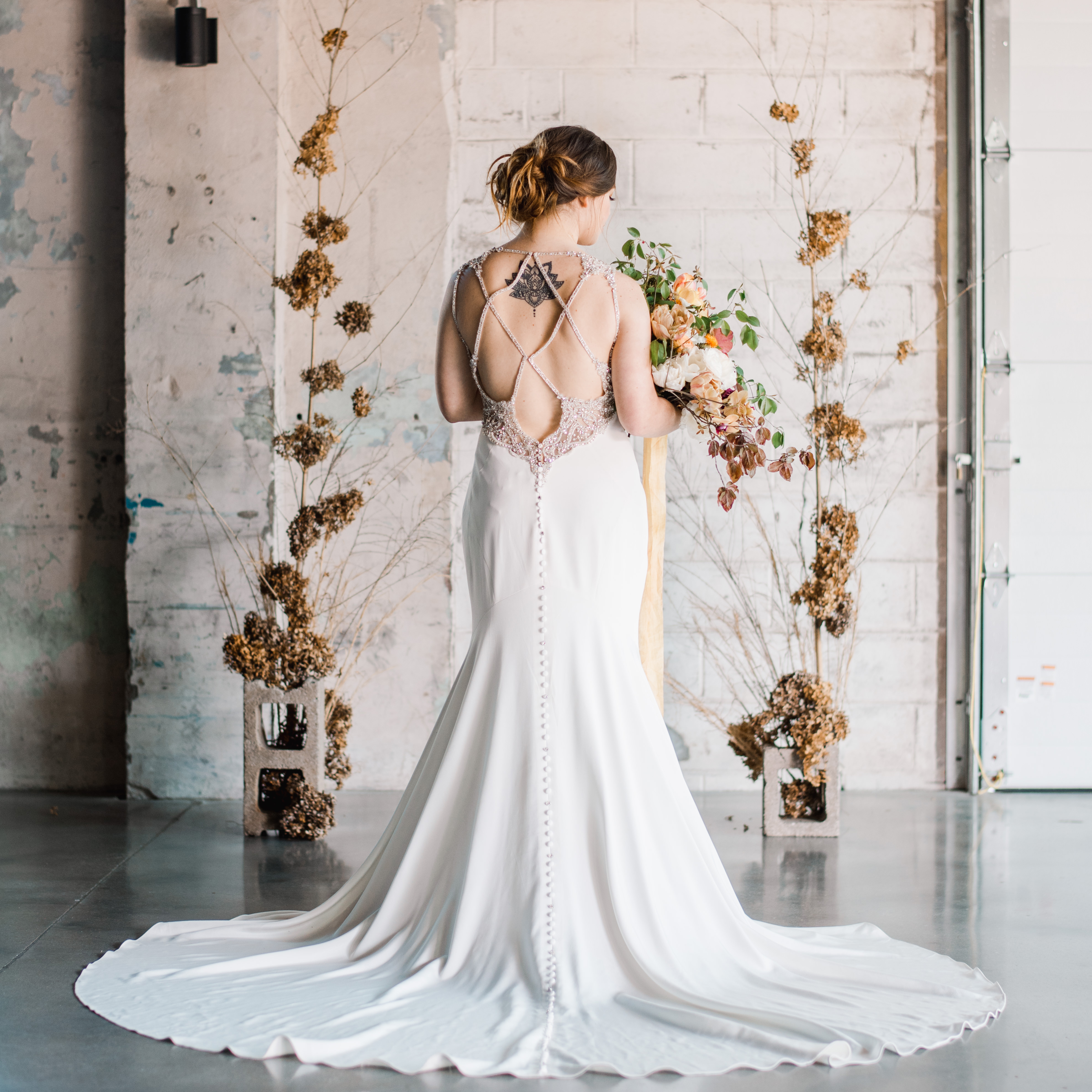 bride with open back dress at industrial venue