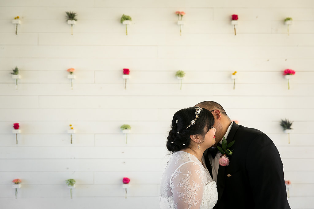Bride and groom kissing in front of flower wall