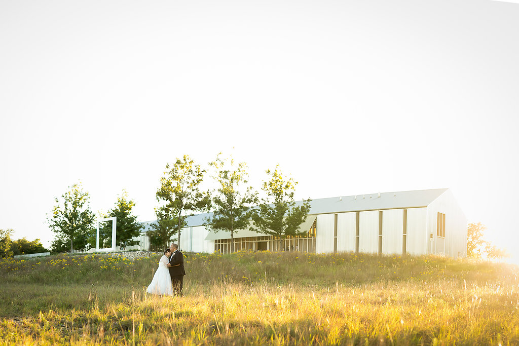 Wedding portraits in a field at sunset