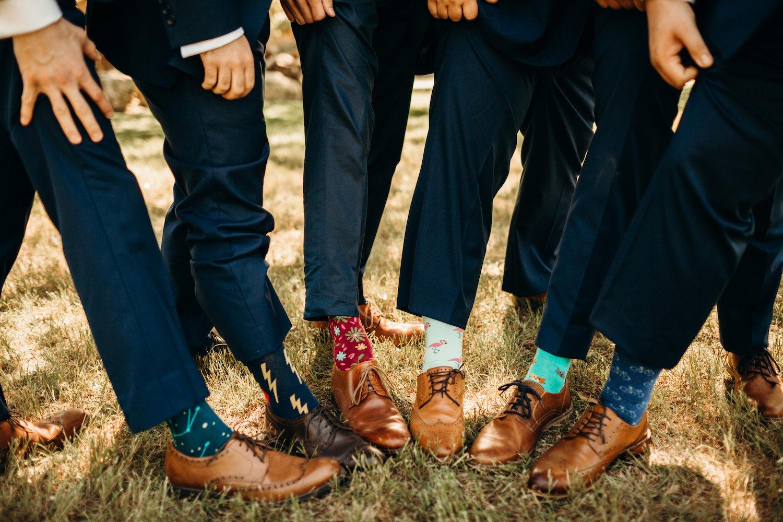 groomsmen and groom showing fun socks
