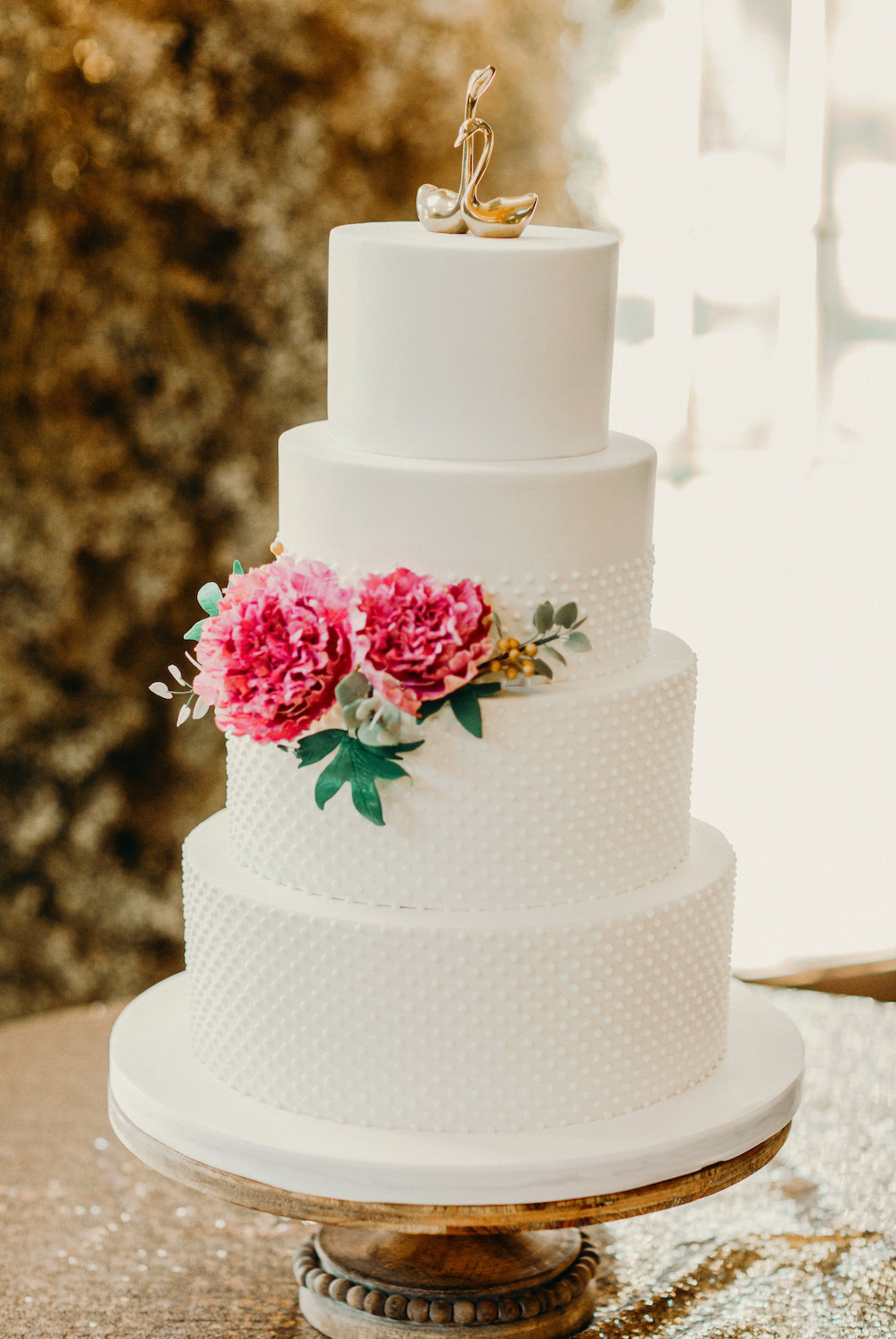 White studded wedding cake with brass swan topper