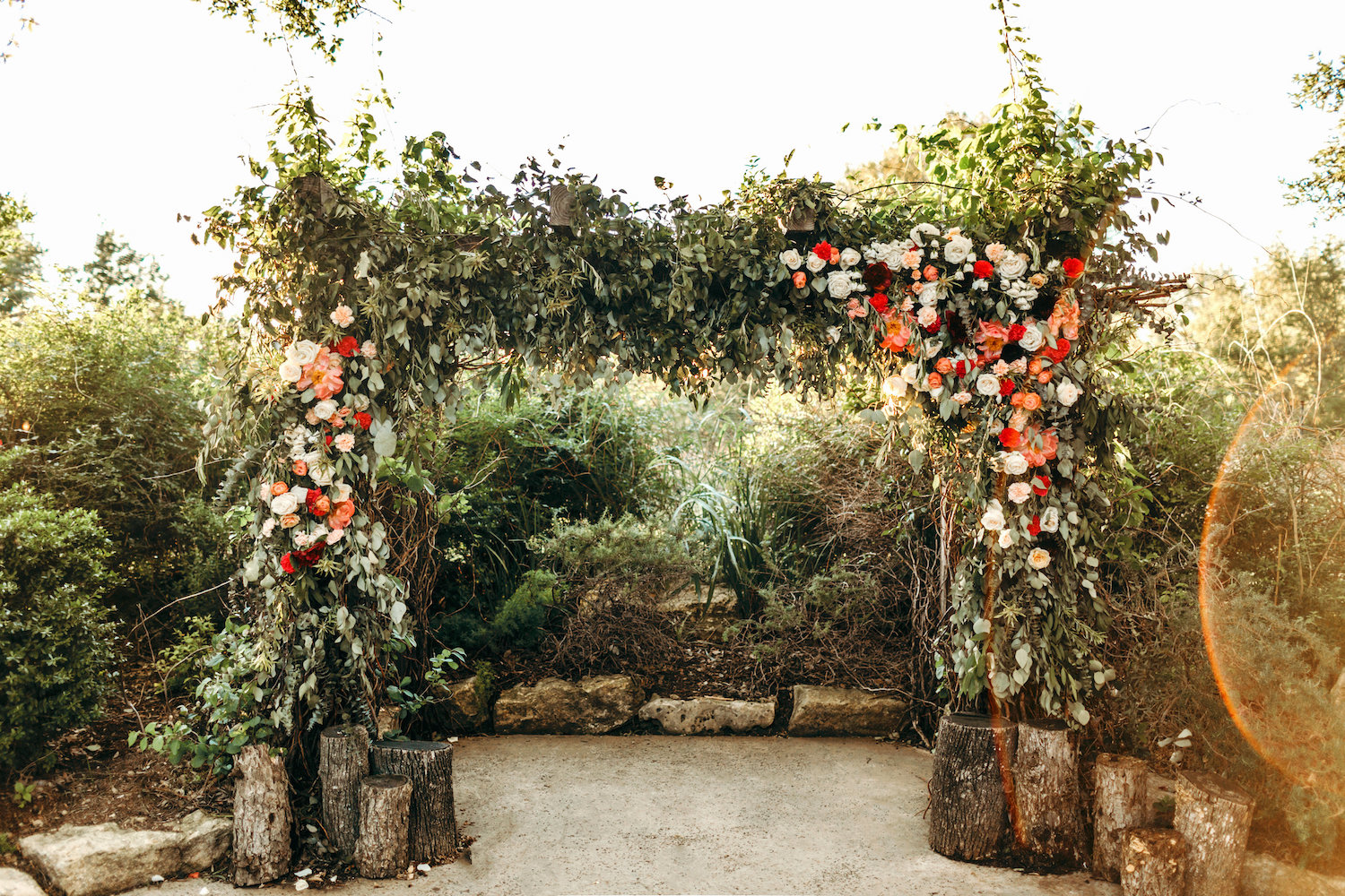 Wedding arch covered in greenery and peach and red flowers