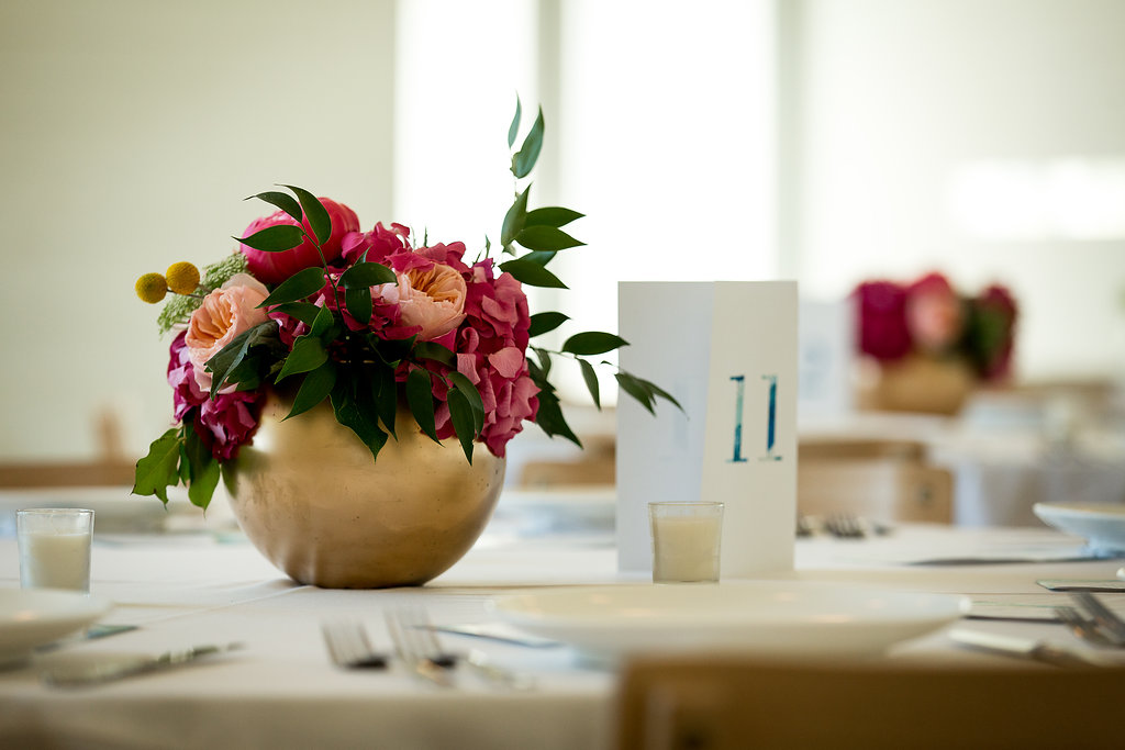 Round gold vase with bright flowers on wedding dinner table