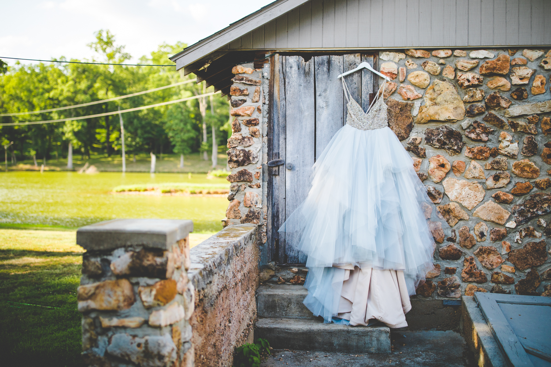 Hailey Paige wedding dress hanging on barn in Southwest Missouri