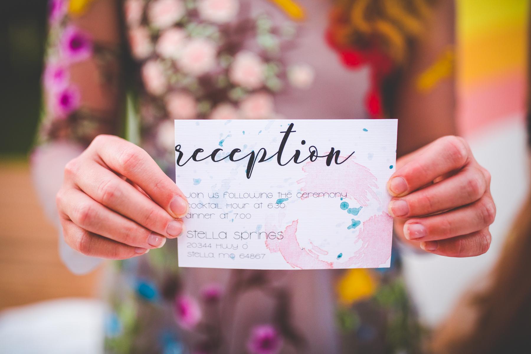 Bridesmaid holding a watercolor wedding invitation