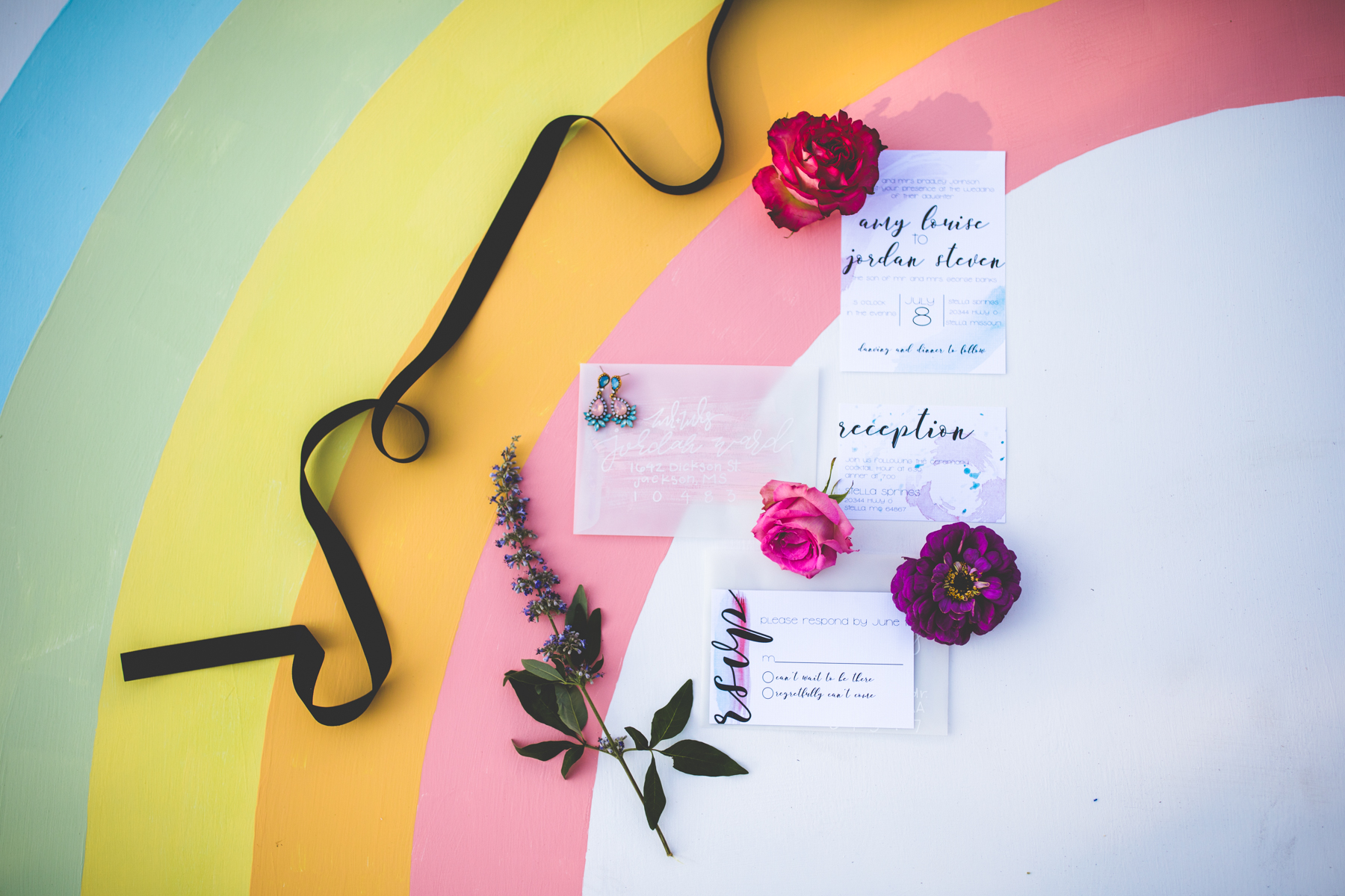 Watercolor wedding invitations set up on rainbow backdrop