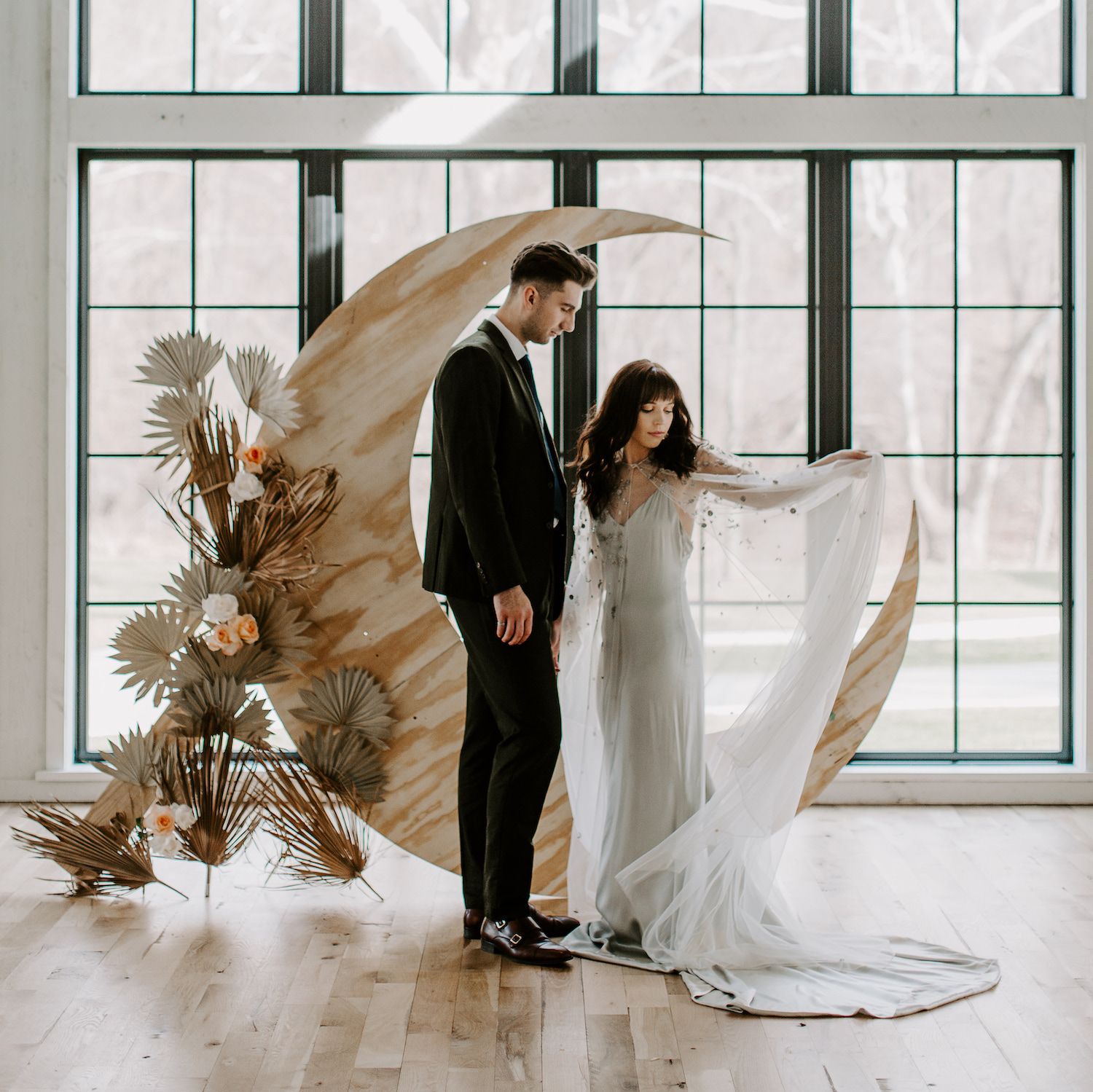 bride and groom in front of wood moon