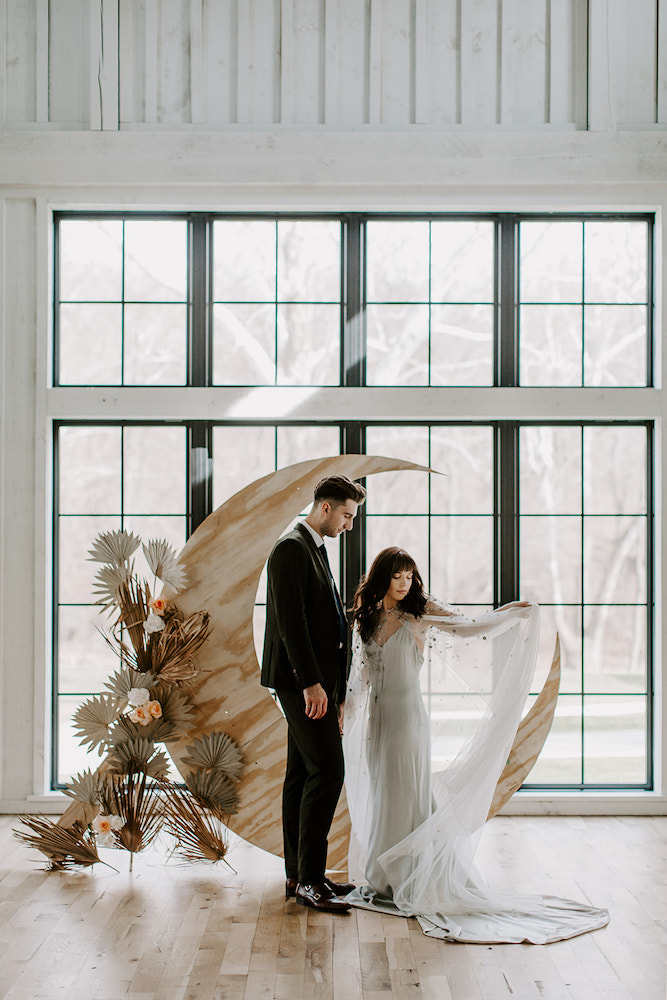 Bride and groom in front of moon with celestial cape