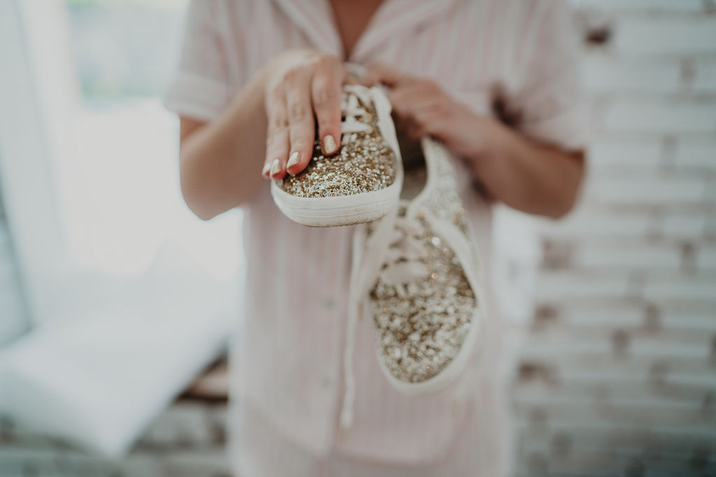 Bride holding gold sparkly keds in Northwest Arkansas wedding