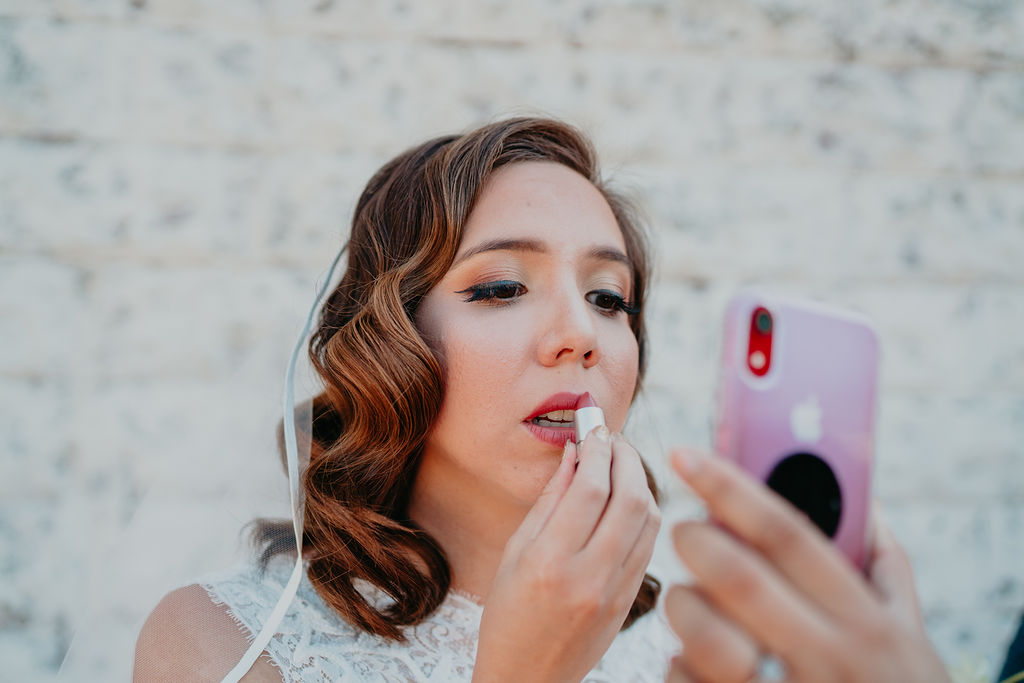 bride reapplies lipstick using phone as mirror