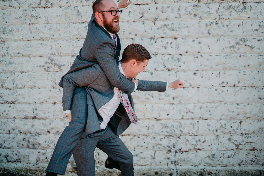 groom rides groomsmen in goofy portrait