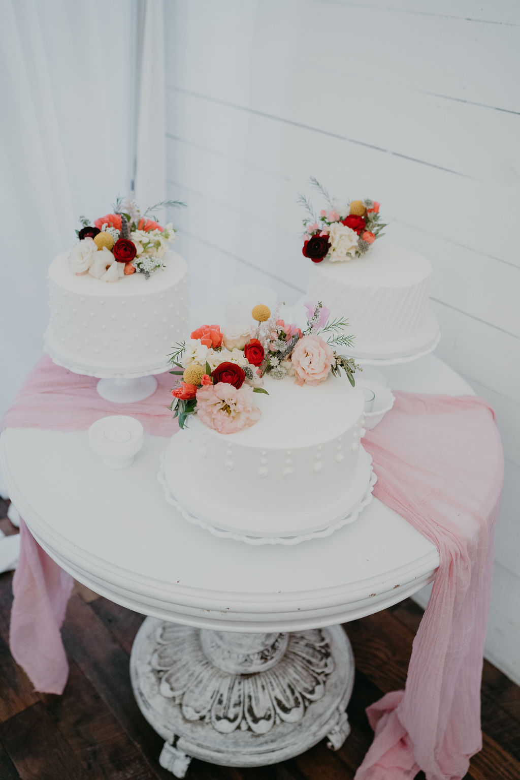 Three white cakes with bright flowers from Earth and Honey in Northwest Arkansas