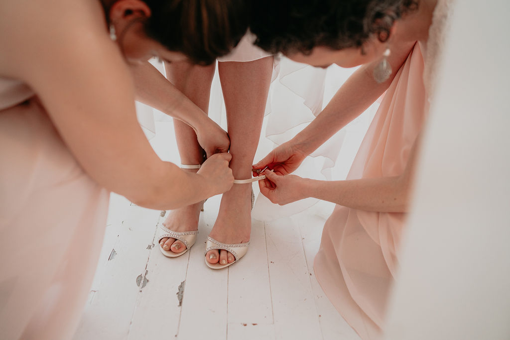 Two bridesmaids help bride buckle shoes