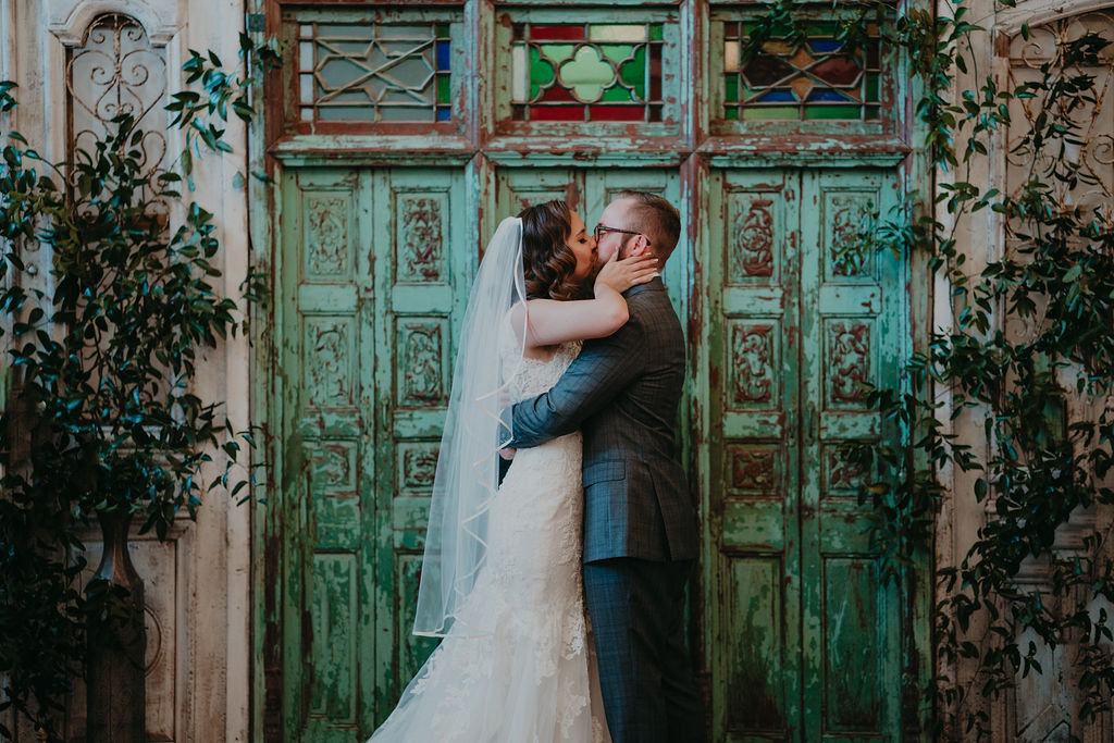 Bride and groom first kiss in front of green doors at The Ravington