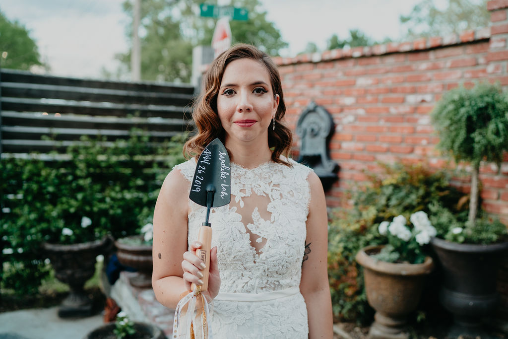 bride holds trowel to unbury bourbon
