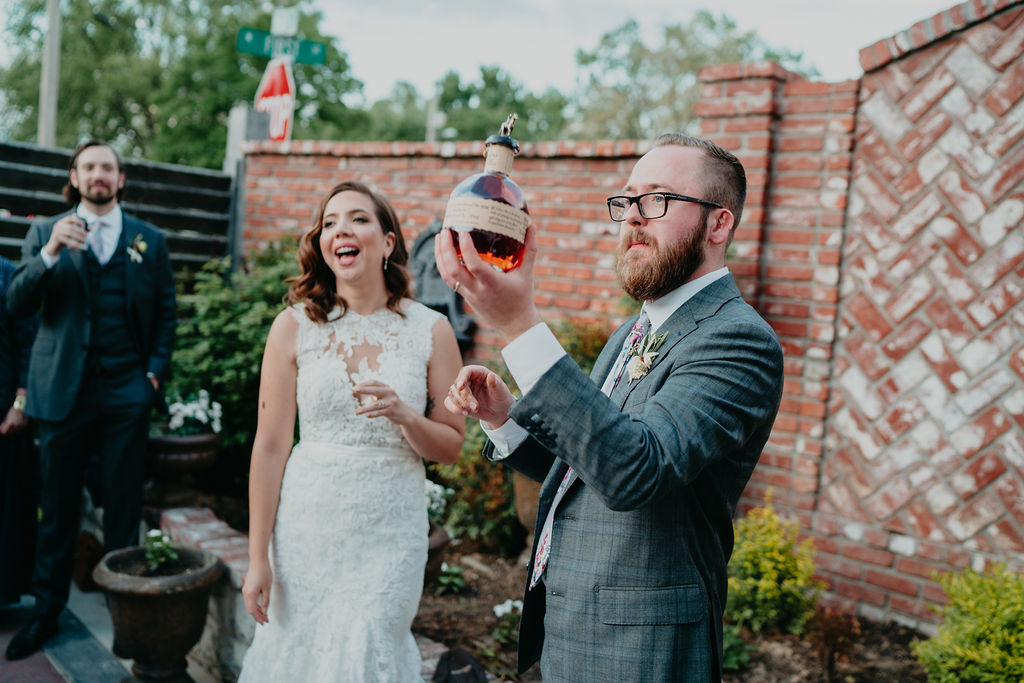 groom holds up bourbon bottle