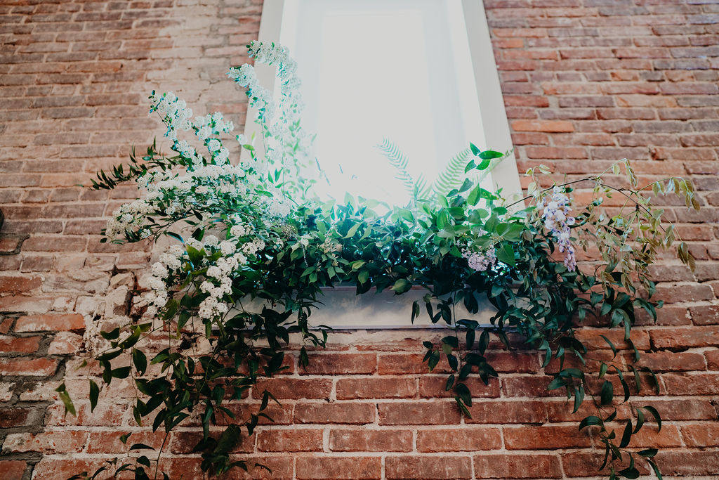 garden wedding florals come down from windows in brick building