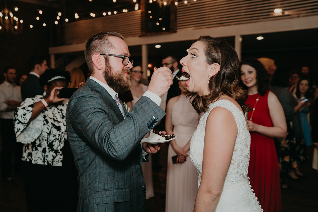 Groom feeds bride bite of cake