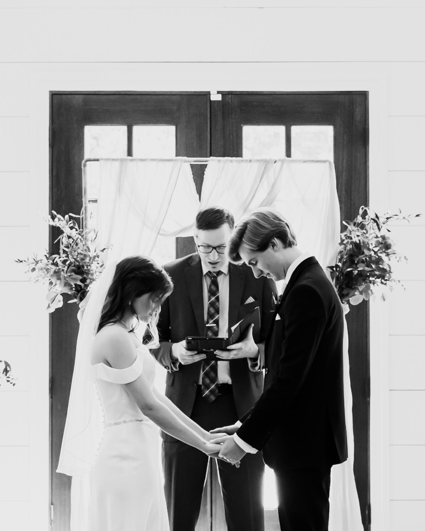 Bride and groom pray at The Loft at Stone Oak