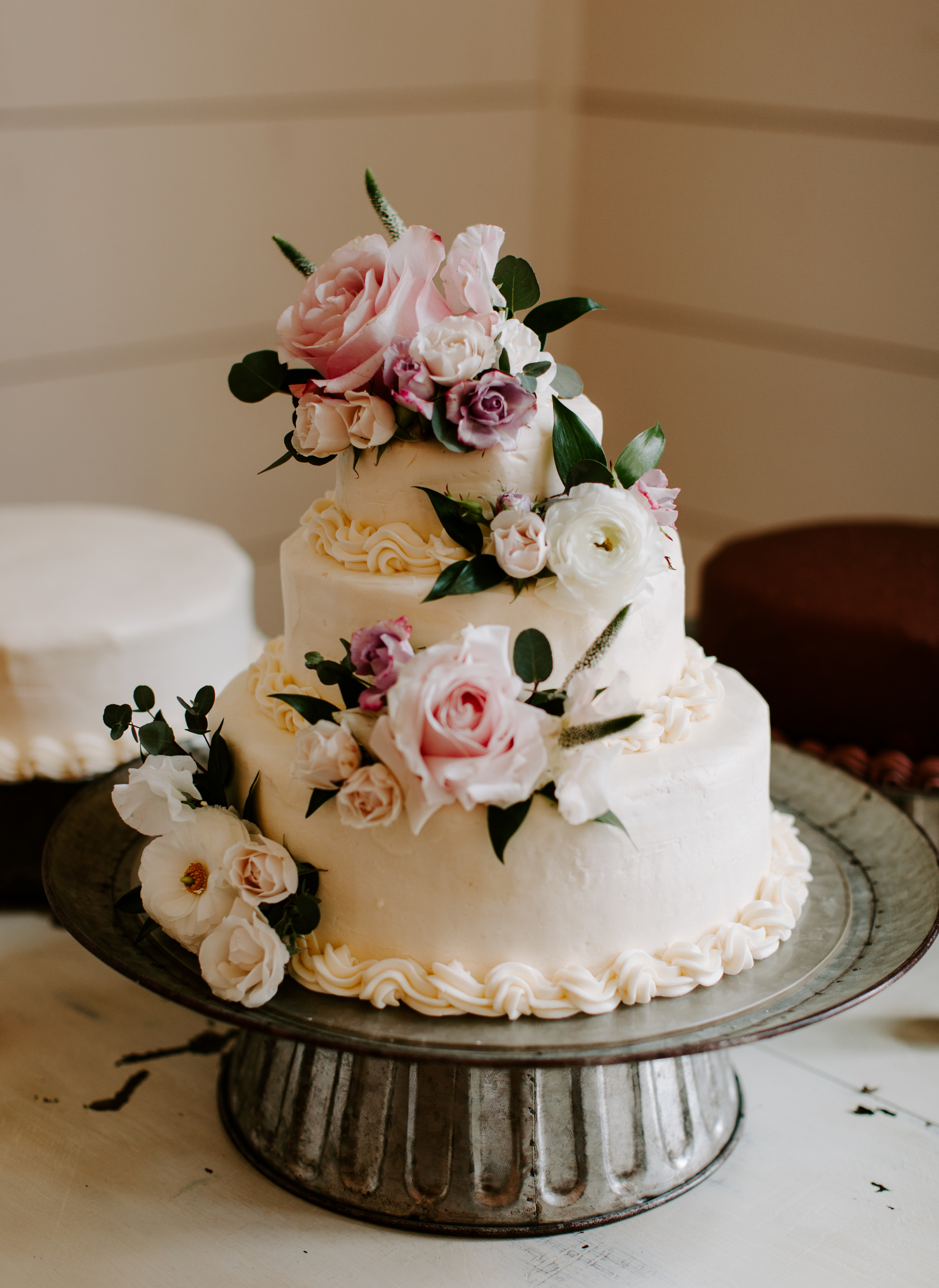 White wedding cake with pink and purple roses