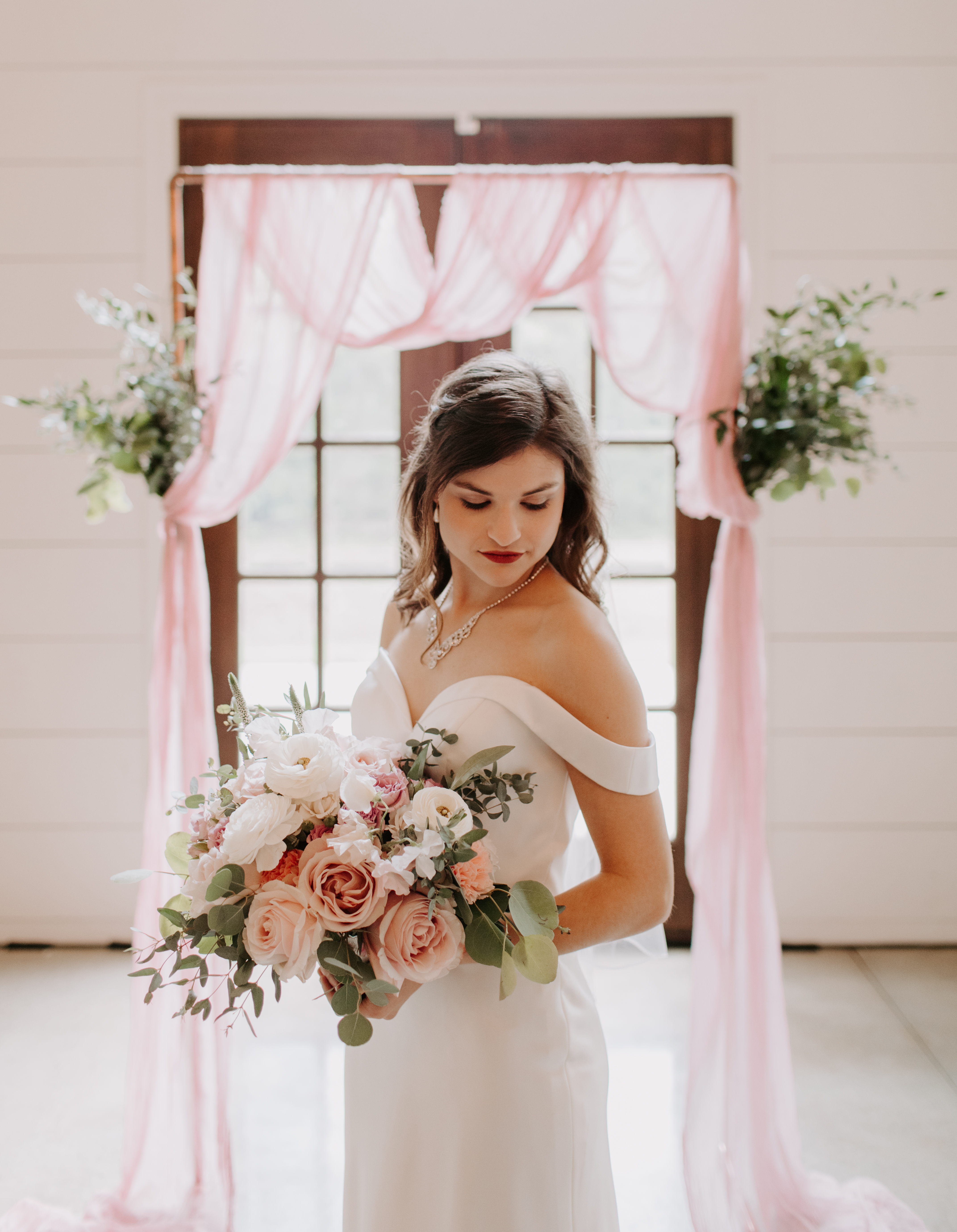 Bridal portrait in front of copper arch with pink cheesecloth and greenery