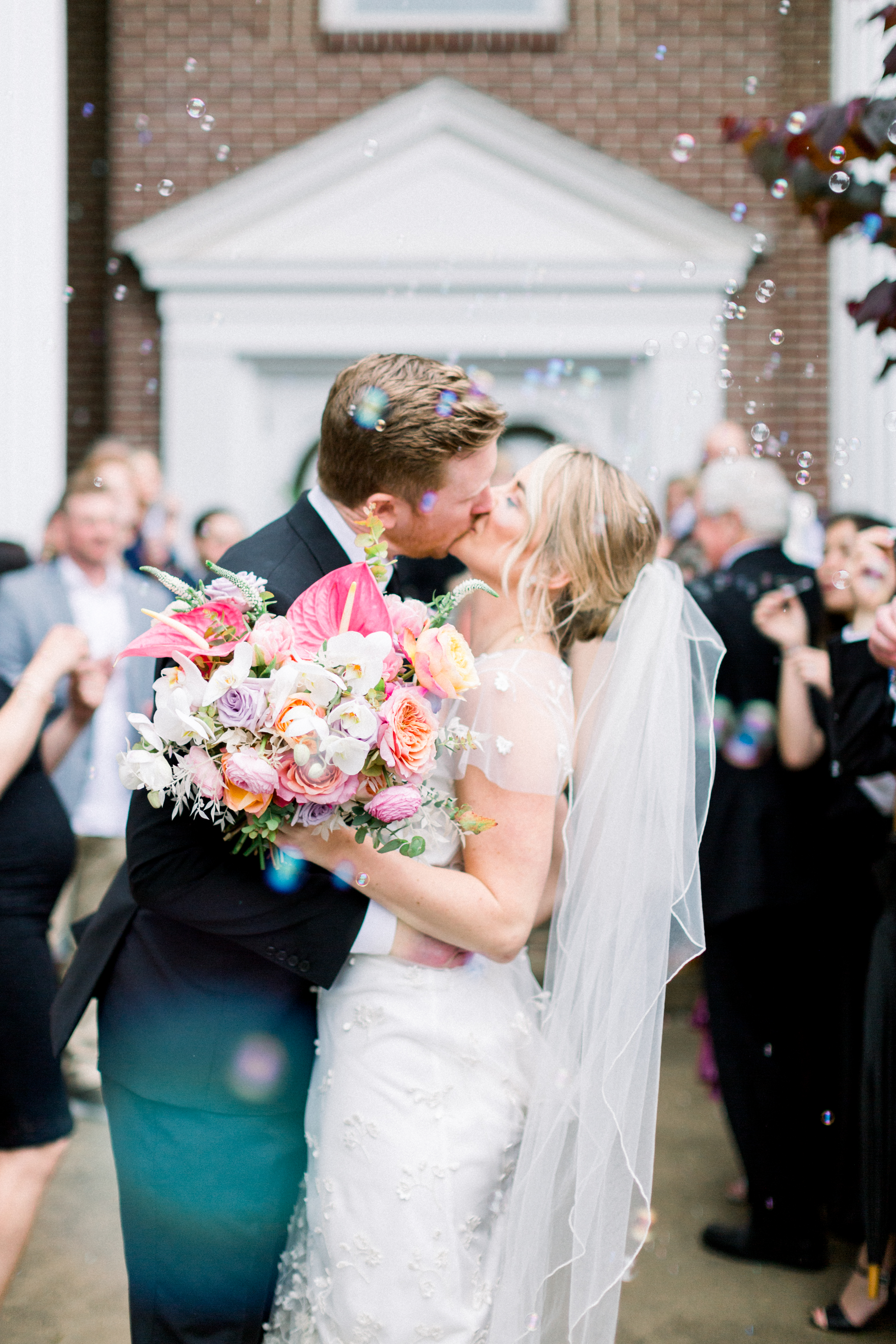 Bride and groom kiss in front of church in Bentonville with bubbles