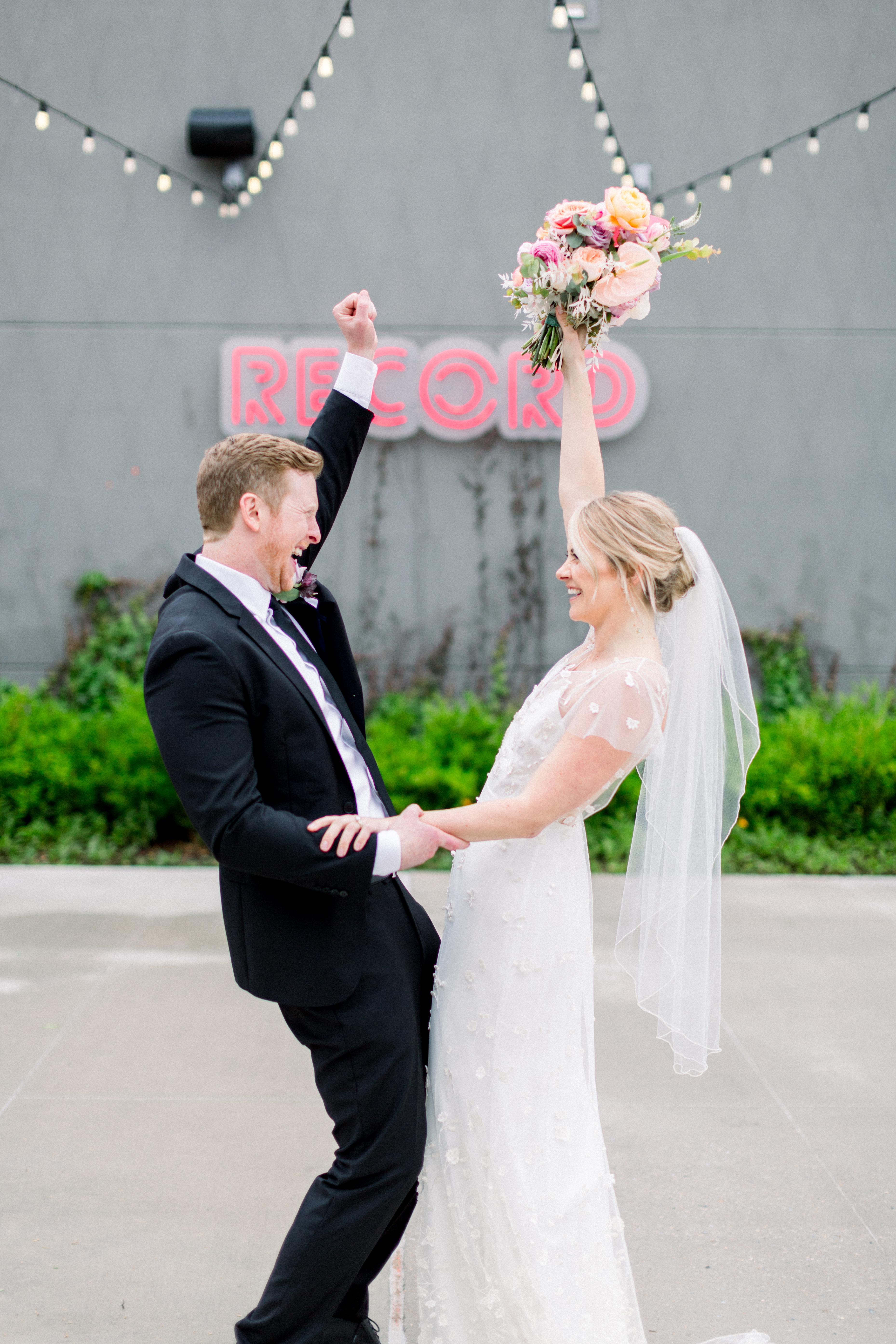 Bride and groom celebrate in front of Record Downtown Bentonville