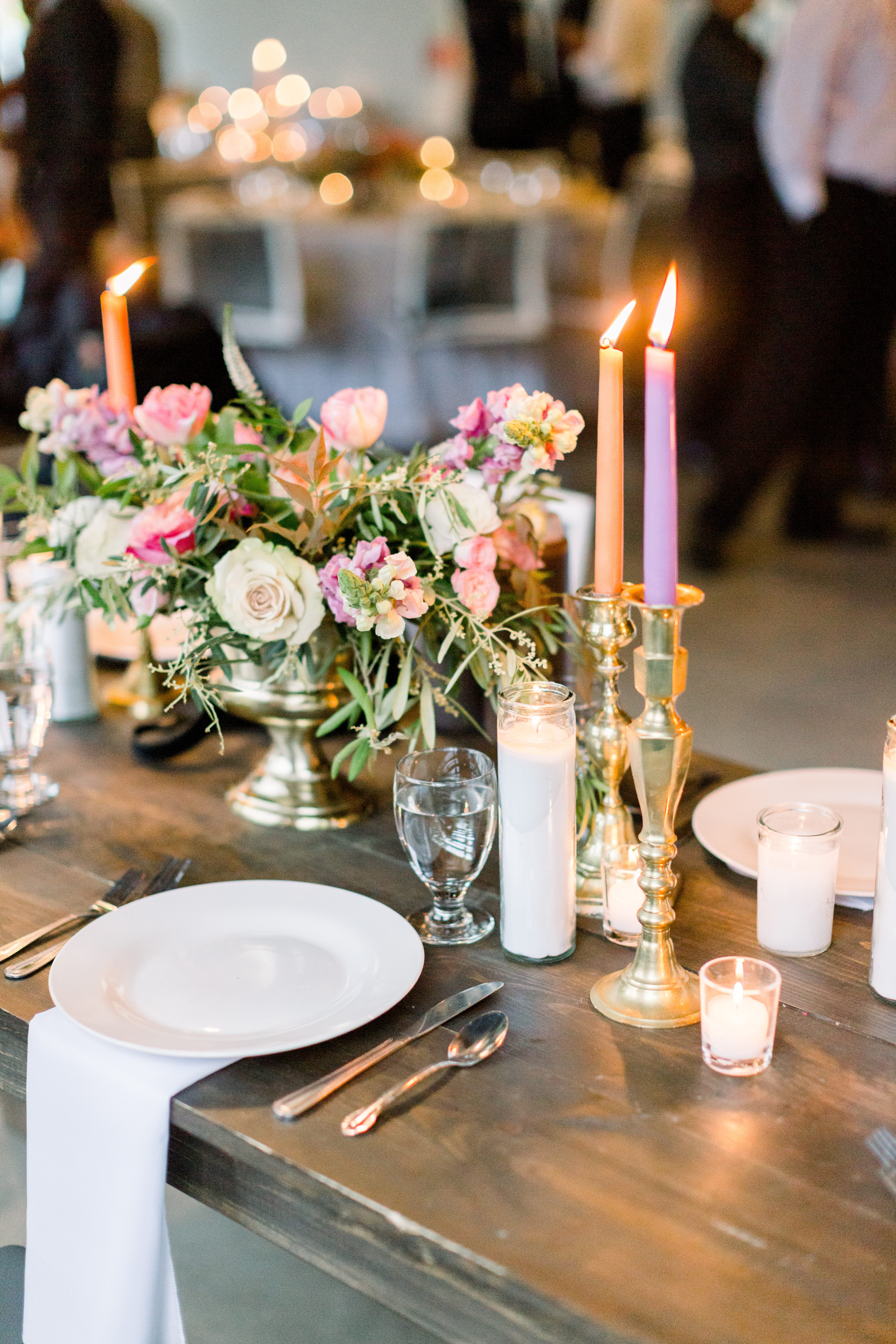 Wooden table with bright candles and flowers at wedding in Northwest Arkansas