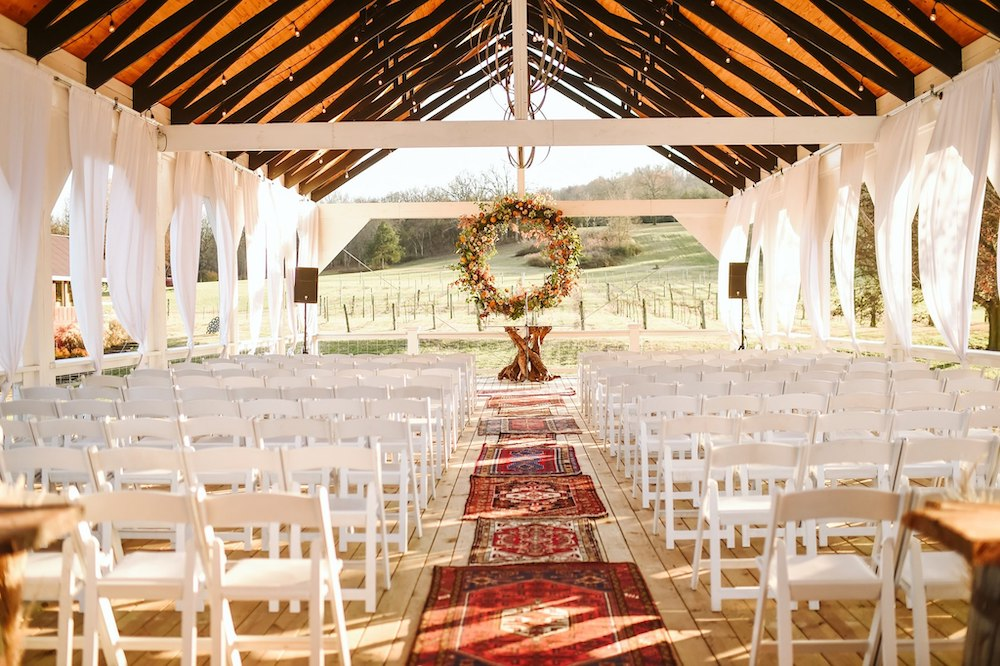 Sassafras Springs Vineyard & Winery Patio Wedding ceremony with boho vintage rugs