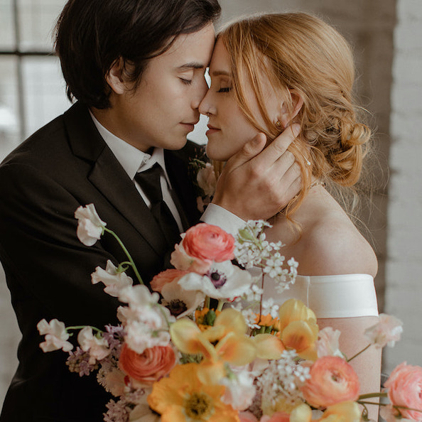 moody photo of bride and groom with bouquet