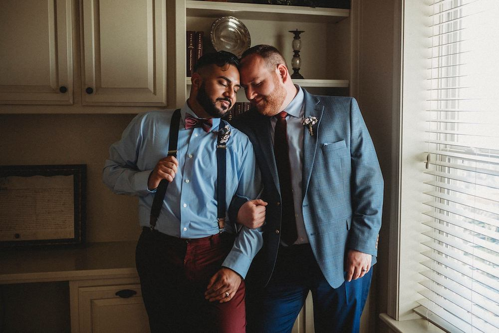 LGBT grooms in maroon and navy with bowtie and suspenders in Fayetteville Arkansas