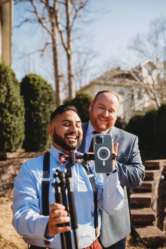 two grooms wave to family watching their covid wedding livestream on iphone