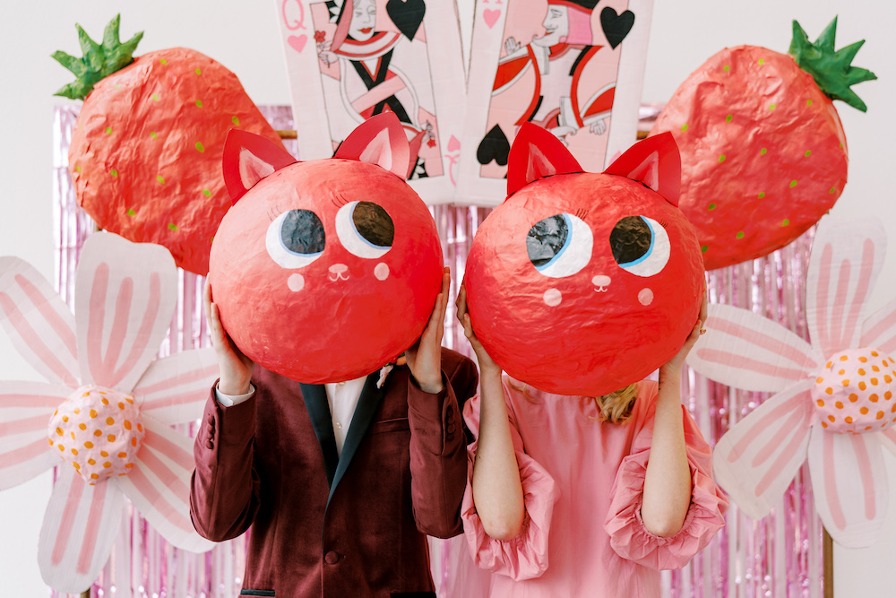wedding couple with paper mache cat heads held up in front of faces