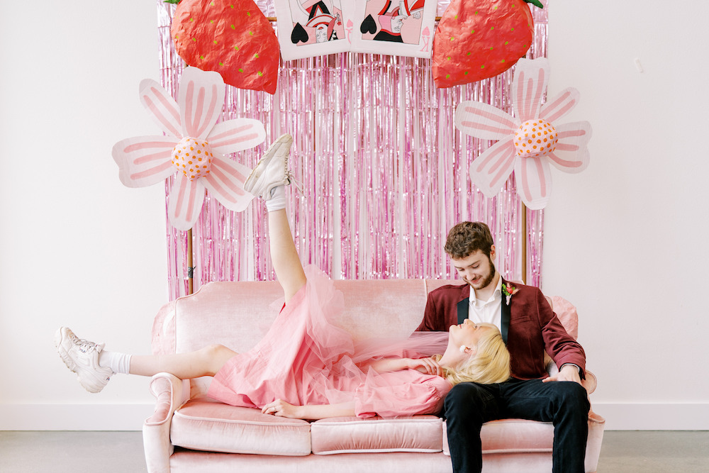 bride in short pink dress and sneakers and pink veil on pink couch