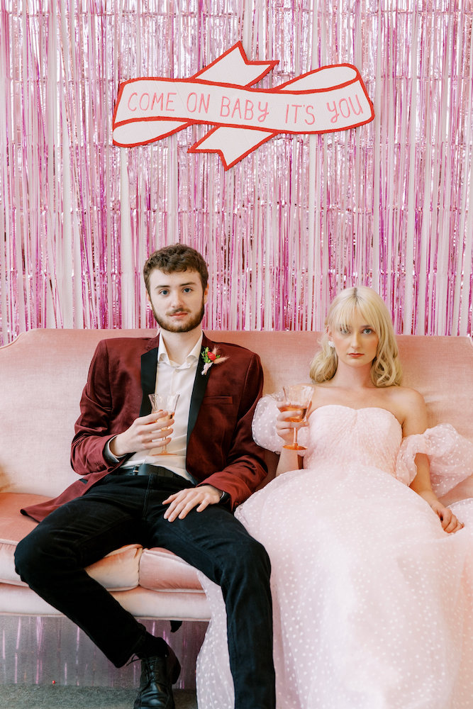 wedding couple slumped on pink couch in front of shiny pink curtain