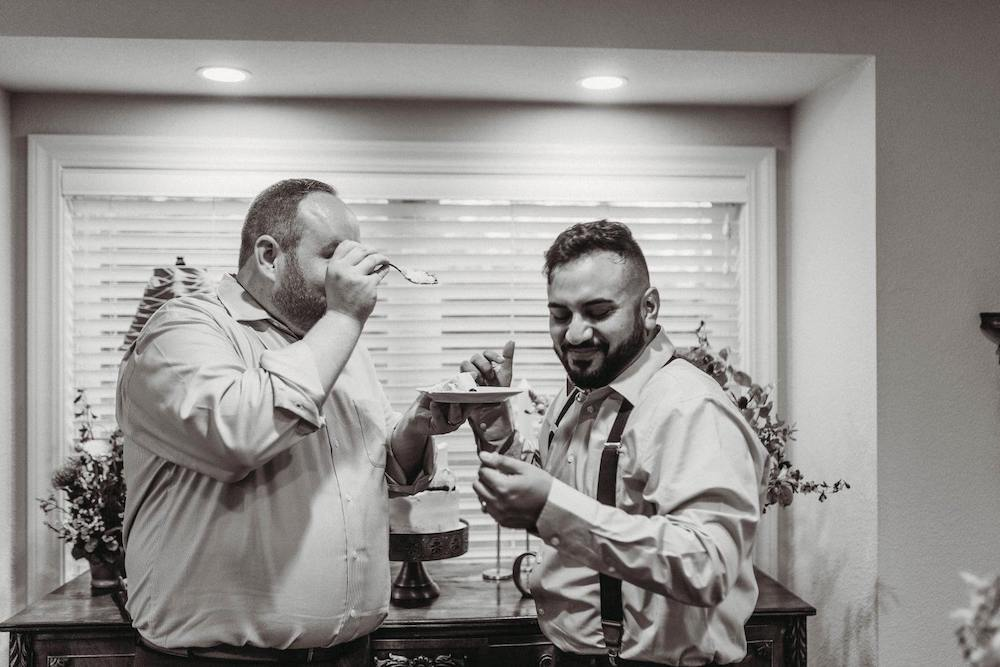 two grooms feed each other cake after wedding NWA